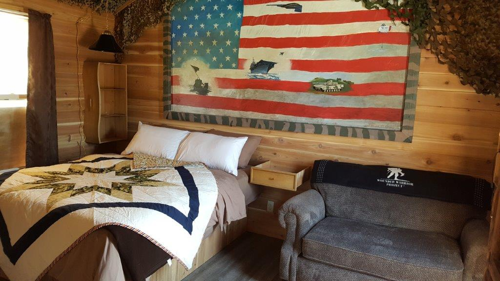 """DELUXE CABIN # 15 - $165/ 2 people, $15 each additional – (Military themed) 1 queen bed, Full size murphy bed, Twin Sofa sleeper, full size futon. Full kitchen, 32' deck. Handicap accessible with grab bars in bathroom, walk-in shower, wheelchair height counters and sinks and 36"""" sliding bath and bedroom doors."""