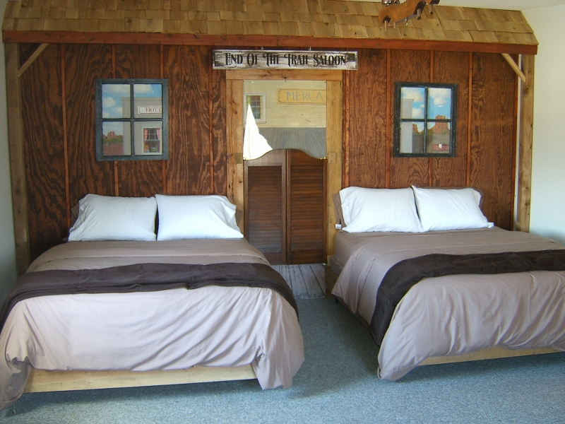 SUITE # 2 – Camp Cheyenne Kitchen Suite -  $75/1 person, $15 for each additional -  Located in Main Lodge – (Camp Cheyenne) -Western themed – End of the Trail – Full kitchen – 3 queen beds, full size futon (Can be rented with adjoining door to Room # 3 to make 3 bedrooms with 2 baths for $115/ 2 people